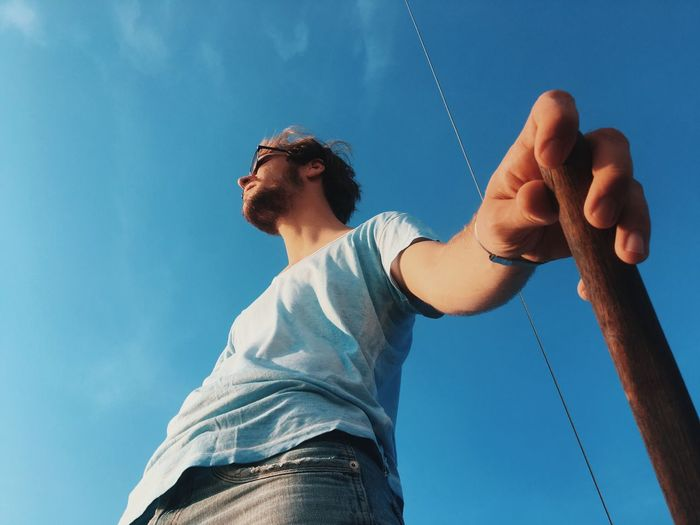 Low angle view of man holding stick against sky