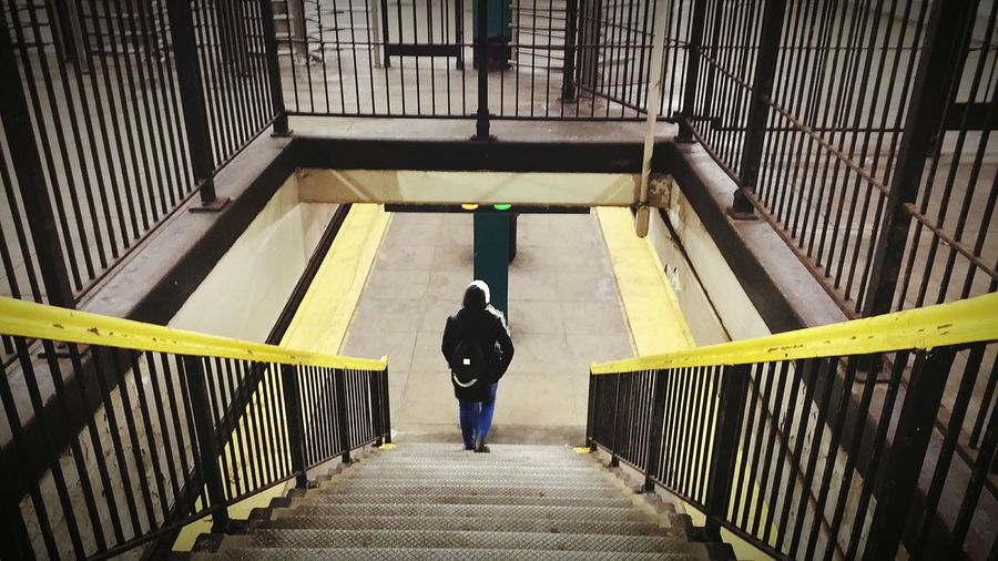 Rear view of person moving down on steps at railroad station