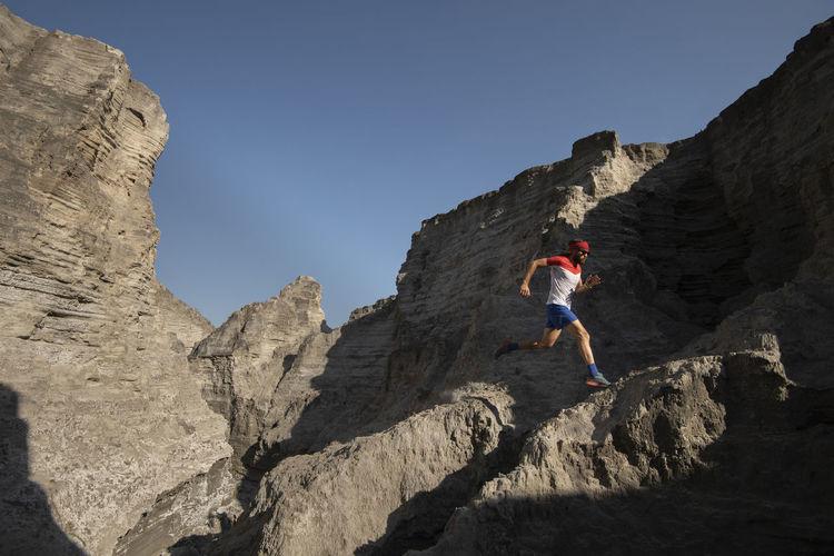 Full length of person on rocks against sky