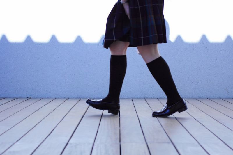 Low section of schoolgirl walking on footpath against wall