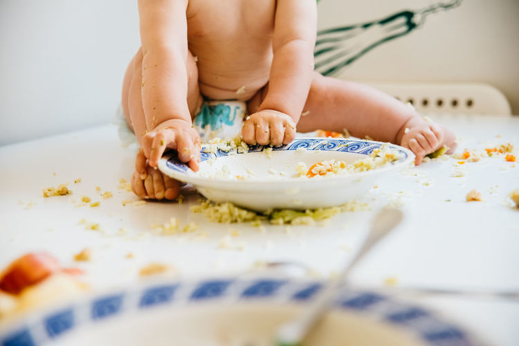 Low section of baby girl eating food on table at home