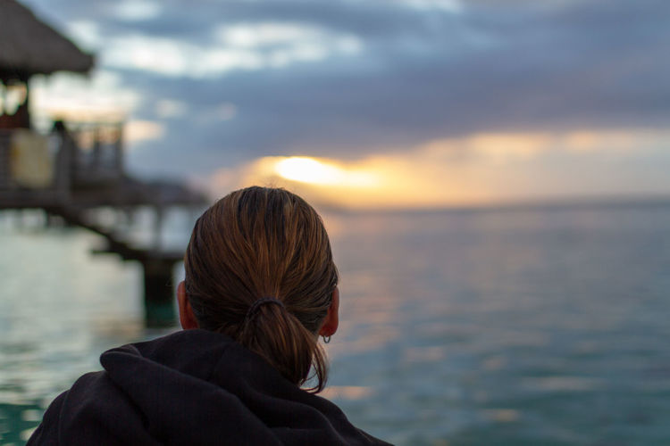 Rear view of woman by sea against sky during sunset
