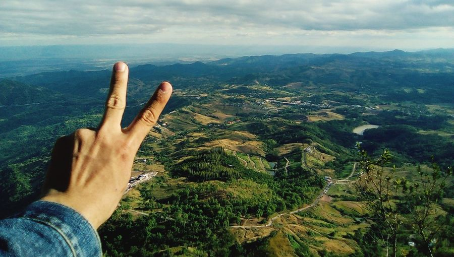 Cropped Hand Gesturing Peace Sign Against Landscape