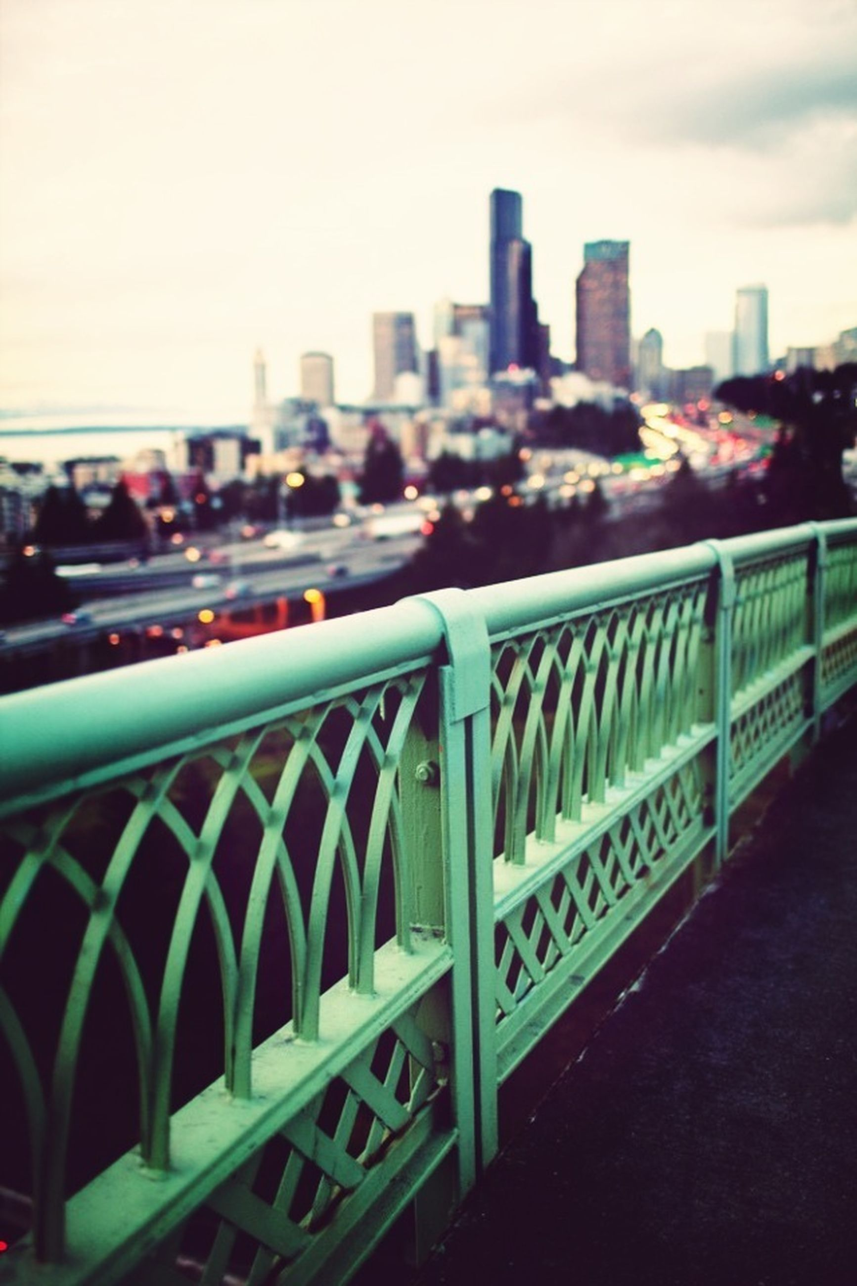 railing, city, architecture, built structure, building exterior, focus on foreground, bridge - man made structure, cityscape, metal, sky, river, fence, connection, bridge, city life, outdoors, day, selective focus, skyscraper, no people
