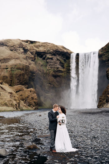 Rear view of couple kissing in water