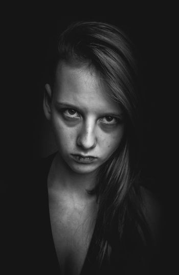 Close-Up Of Angry Young Woman Against Black Background