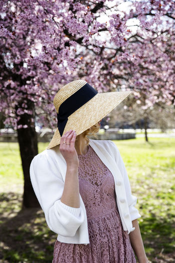 Low section of woman standing on cherry blossom
