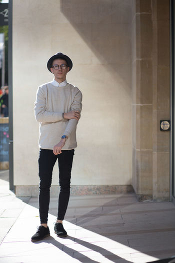 Man in stone jumper, hat and glasses in the city. Adult Adults Only Birmingham Black Trousers Business Collar Cream Day Fashion Glasses Hat Jumper Man Men Menswear One Person People Smart Standing Stone Street Style Stylish Tattoo