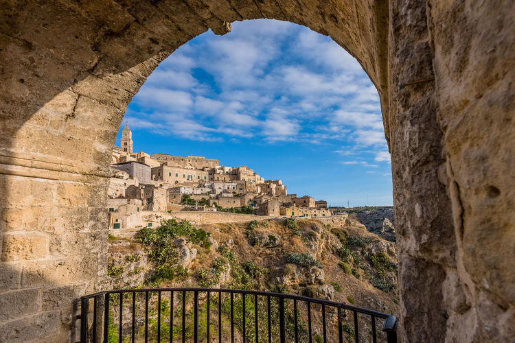 Low angle view of buildings seen through arch at sassi di matera