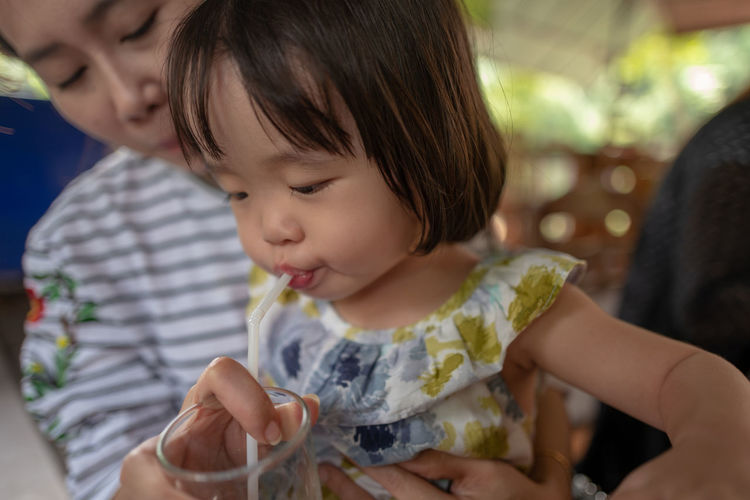 Midsection of woman feeding daughter water in glass