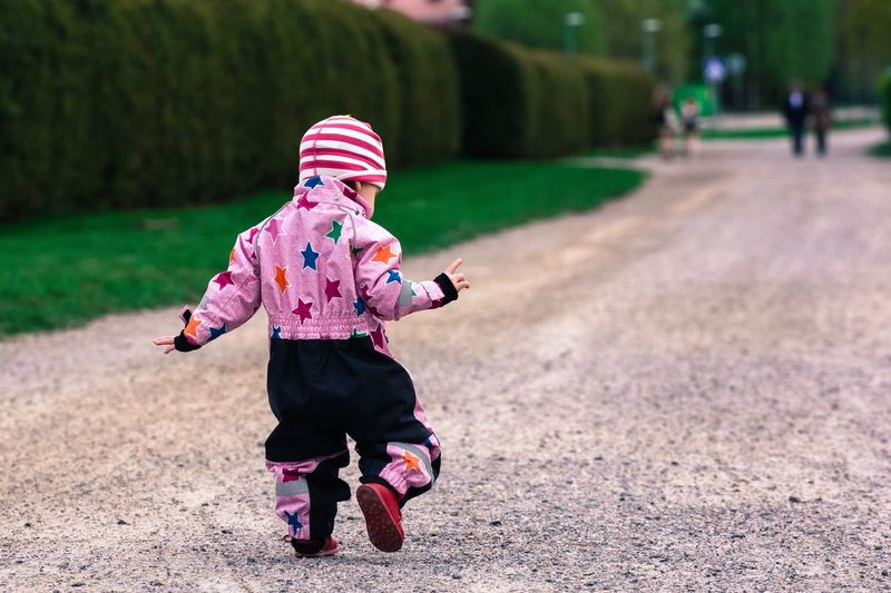 Rear view full length of baby girl on pathway at park