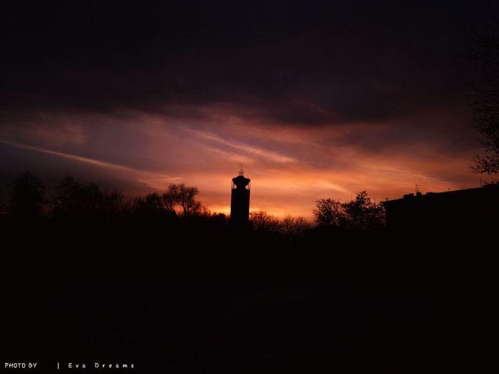 Silhouette of lighthouse against orange sky