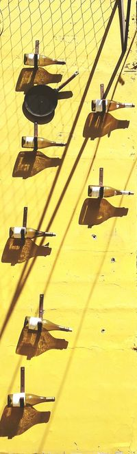 Empty wine bottles on yellow wall during sunny day