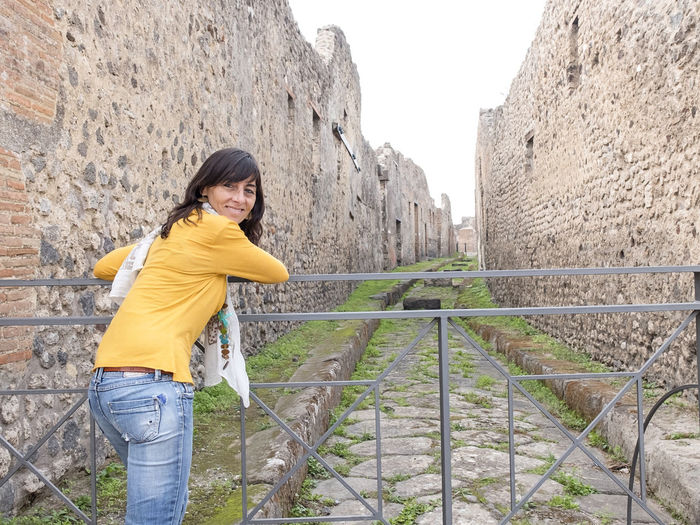 Portrait of woman standing by railing against stone wall