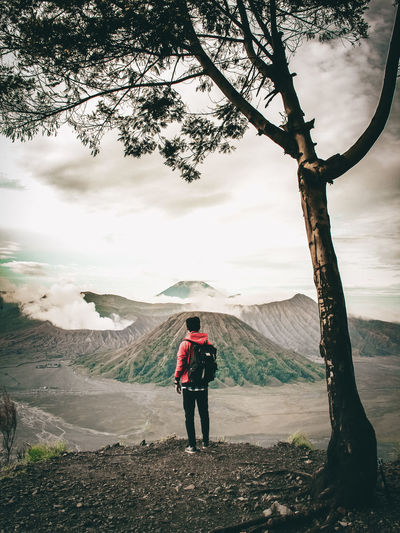 Full Length Of Backpacker Looking At Mountains While Standing On Field Against Sky