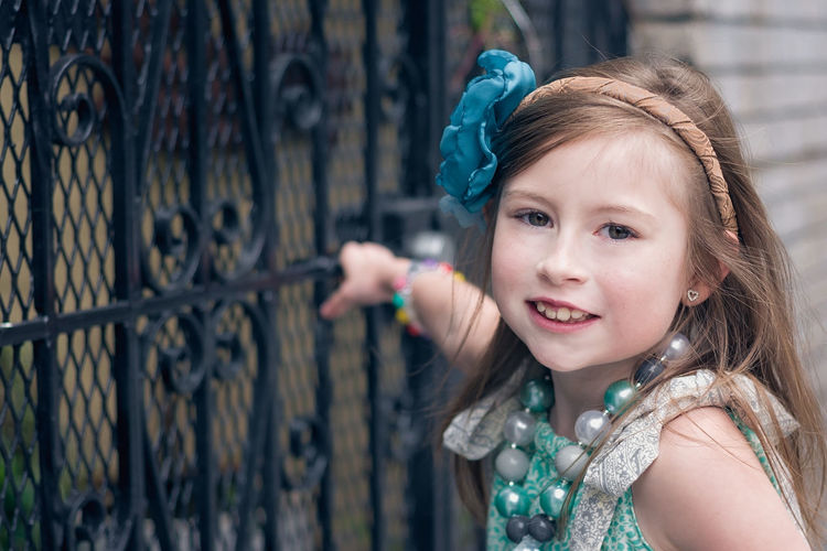 Portrait of cute girl standing by gate