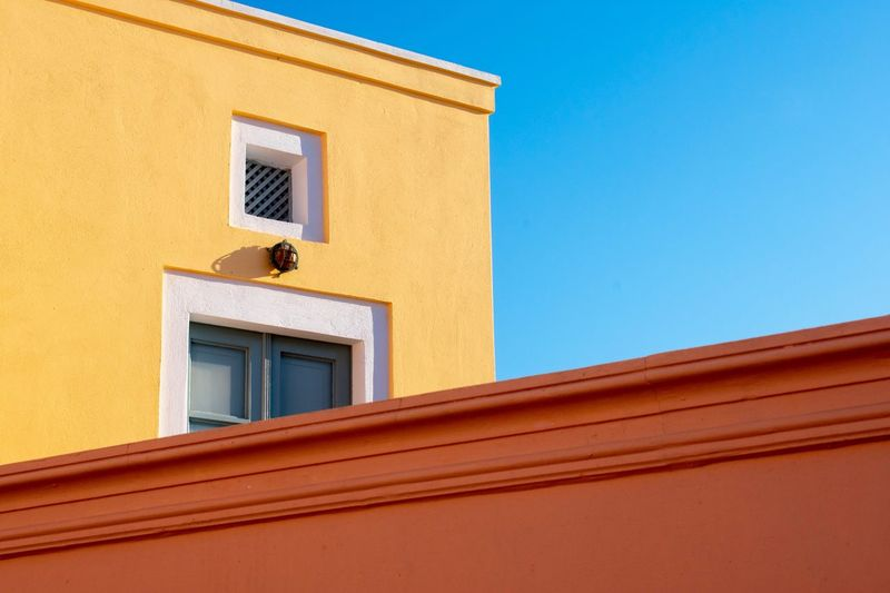 Simplicity Yellow Orange Color Window Door Eyemphotography Minimalism EyEmNewHere Angle Shapes EyeEm Selects Architecture Built Structure Building Exterior Building Low Angle View Window Blue No People Day Wall - Building Feature Yellow House Clear Sky Sky Nature Residential District Outdoors Sunlight Wall Copy Space Capture Tomorrow