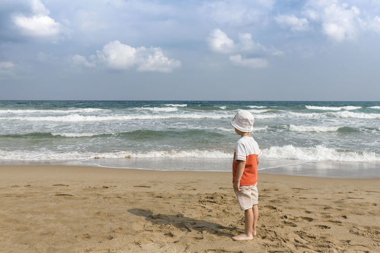 Sea Beach Land Water Sky Horizon Over Water Horizon Full Length Motion Wave Hat Sand One Person Leisure Activity Nature Beauty In Nature Child Casual Clothing Scenics - Nature Sun Hat Outdoors Land Wave Childhood Beauty In Nature Nature Hat