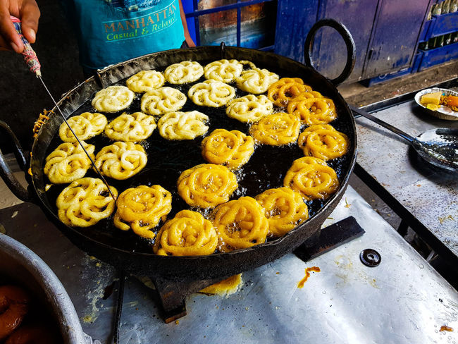 Jalebi an indian sweet dish being fried in sugar syrup in a large container Frying Pans Jalebi Sale Built Structure Day Fried Sweets Frying, Sweet, Dessert, Hot, Sugar, Syrup, Frying Pan, Kadhai, Jalebi, Jilipi, Amriti, India, Imarati, Diwali, Jilebee, White, Festival, Jilabi, Dussehra, Sugary, Crunchy, Orange, Holi, Fry, Indian, Warm, Isolated, Chewy, Zulbia, Snack, Yummy, Jilebi, Foo Hand Human Hands Jilipi kitchen utensils Mid Section Mithai Preparing Retail  Shop Sugar Syrup Sweet Dish