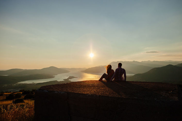 Couple on built structure against sky during sunset