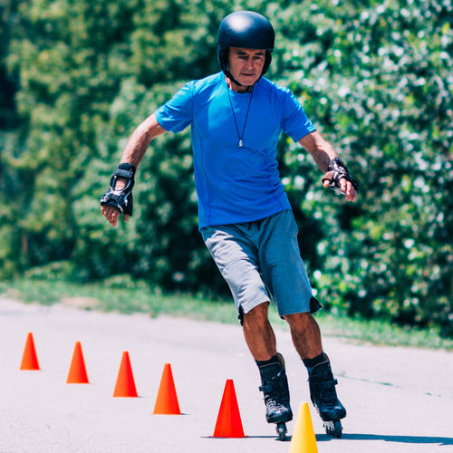 Senior man Roller Skating in Park Rollerskating Grandfather Roller Sport Outdoor Fun Instructor Cones Active Ride Rollerblading Learning Teaching Roller Skating Senior Skate Happy Blade Rollerblade Road Summer Skater Park Activity Smile Helmet Blades Rollerblader Family Protector Recreation  Protection Safe Sporty Enjoy Rollerblades Balance Old Man People Roller Skate Men Leisure Activity One Person Day Outdoors Nature Effort