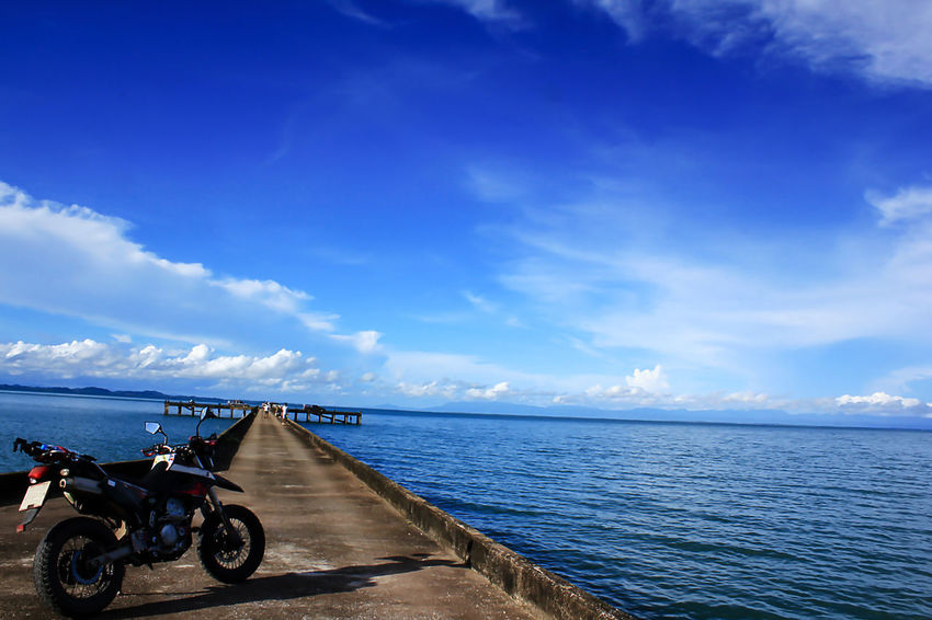 Motorcycles are on the bridge to the sea. Beach Beauty In Nature Blue Cloud - Sky Day Horizon Horizon Over Water Land Land Vehicle Landscape Sea Landscape Sea Nature Outdoors Landscape Seascape Mode Of Transportation Motorcycles Motorcycles Lover Nature Outdoors Scenics - Nature Sea Sky Tranquil Scene Tranquility Transportation Water