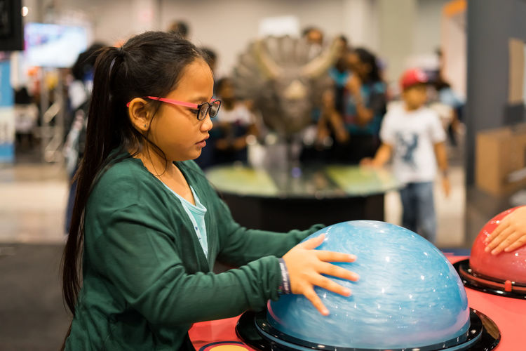 Side view of girl touching tesla ball on table