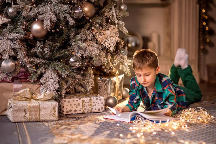 Full length of boy in illuminated christmas tree