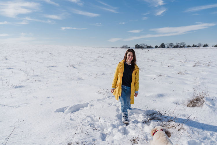 Portrait of man standing on snow field against sky