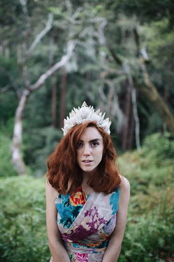Portrait Of Redhead Woman Wearing Headwear Against Trees