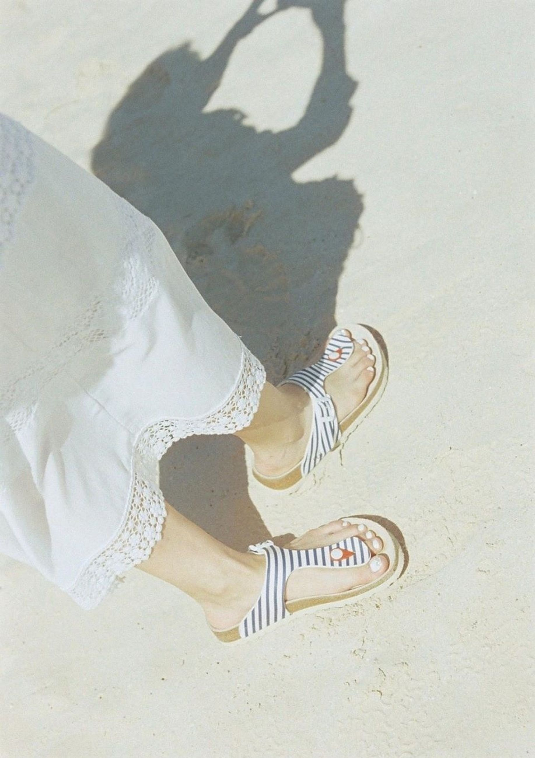 low section, shoe, person, footwear, high angle view, lifestyles, standing, leisure activity, human foot, shadow, sand, casual clothing, day, sunlight, outdoors, white color, canvas shoe