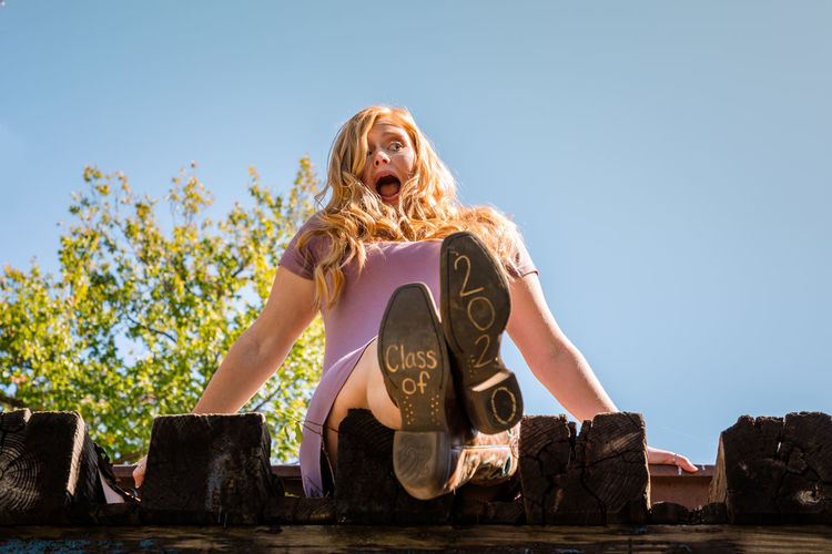 Low angle view of girl sitting on rooftop with text on sole of shoe