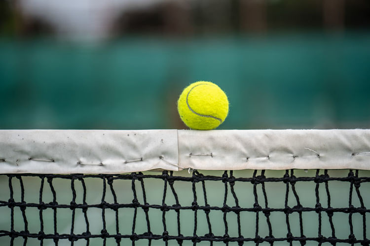 Close-up of tennis ball on net