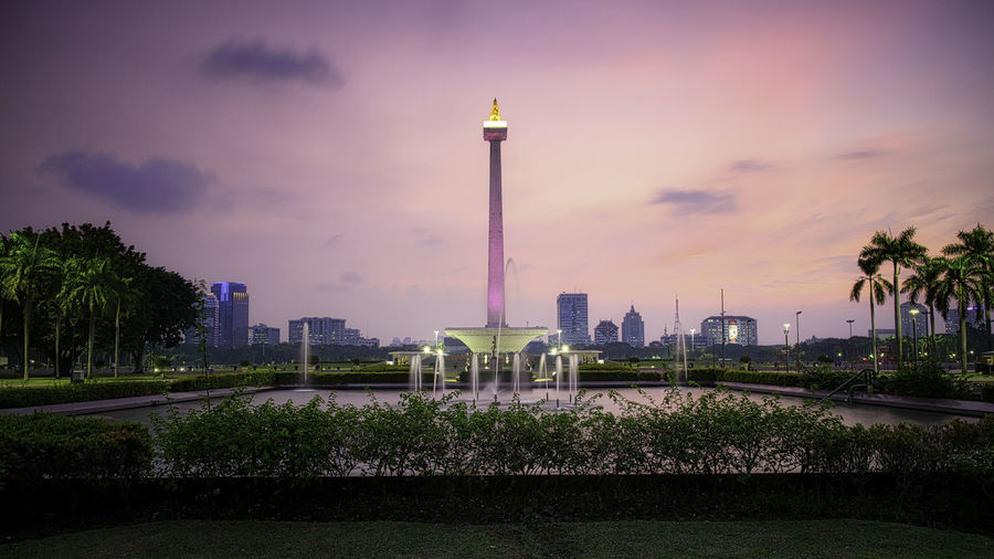 Monas Sunset Architectural Column Architecture Building Building Exterior Built Structure City Cloud - Sky Nature No People Office Building Exterior Outdoors Plant Sky Skyscraper Sunset Tall - High Tourism Tower Travel Travel Destinations Tree Water The Traveler - 2018 EyeEm Awards