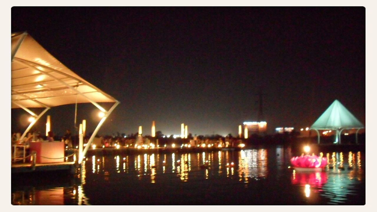 illuminated, night, water, architecture, built structure, building exterior, reflection, waterfront, outdoors, clear sky, no people, sea, sky, city, nature
