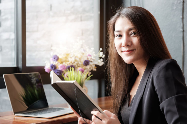 Portrait of beautiful woman holding book by laptop on table