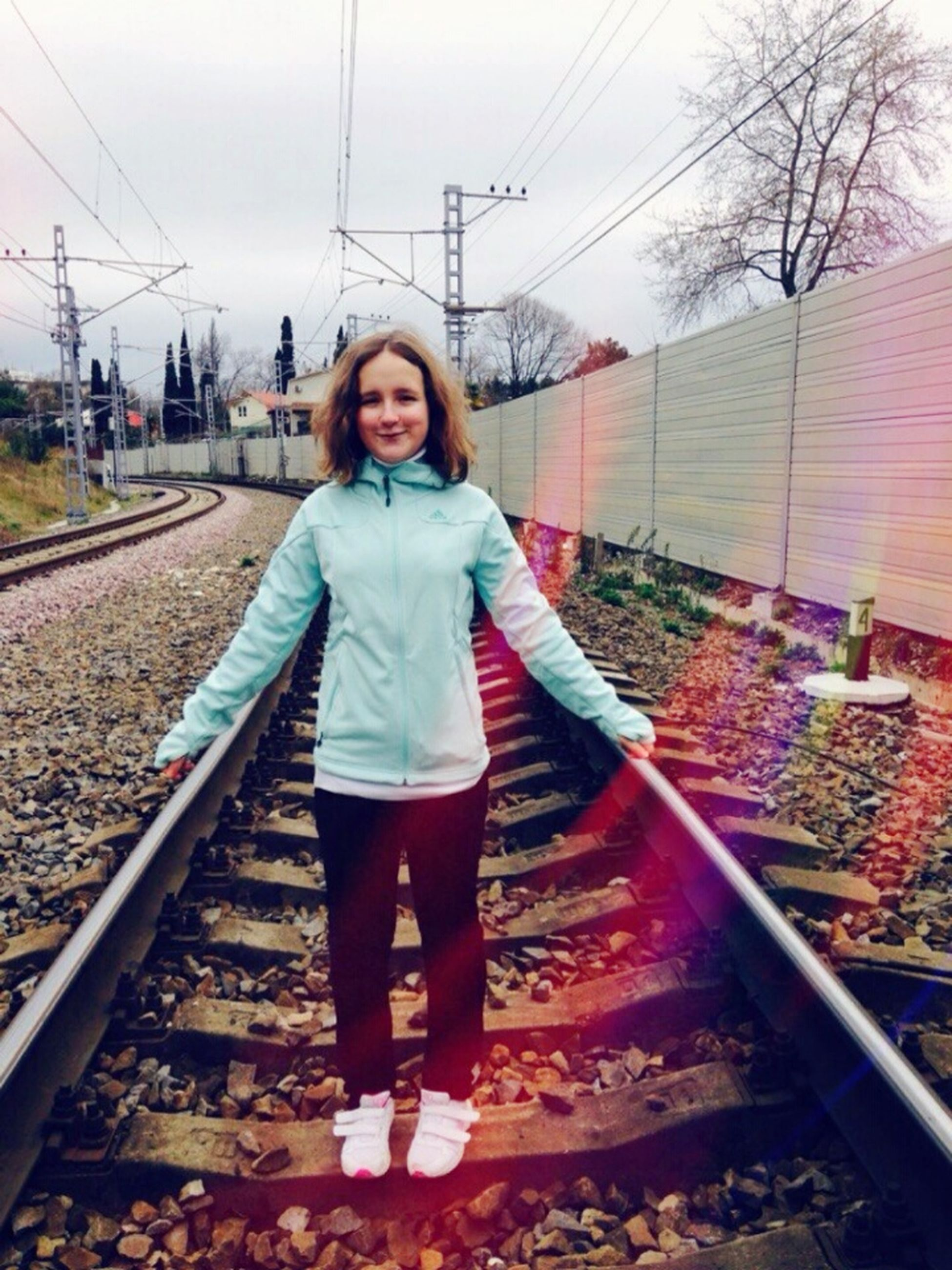 looking at camera, person, casual clothing, portrait, lifestyles, full length, railroad track, front view, standing, young adult, smiling, leisure activity, warm clothing, transportation, happiness, day, young women