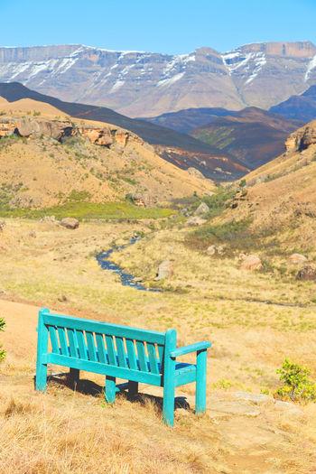 Empty bench on field against mountain range