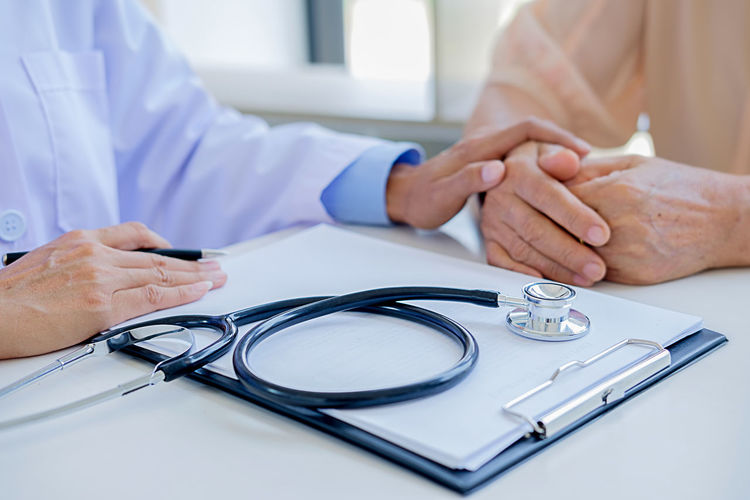 Adult Care Doctor  Expertise Focus On Foreground Hand Healthcare And Medicine Healthcare Worker Holding Human Body Part Human Hand Human Limb Indoors  Lab Coat Medical Equipment Medical Exam Men Midsection Occupation People Real People Responsibility Table Two People Women