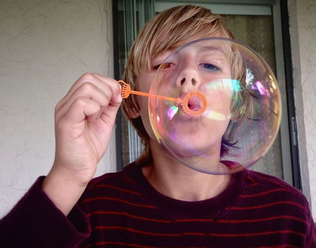 Close-up of teenage boy blowing bubble against wall