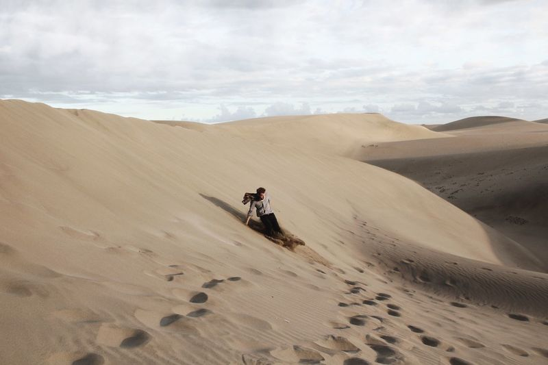 Man On Sand Dune At Desert Against Sky