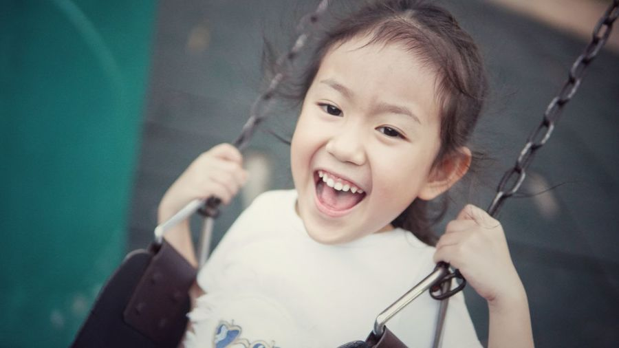 Portrait of smiling girl swinging in playground