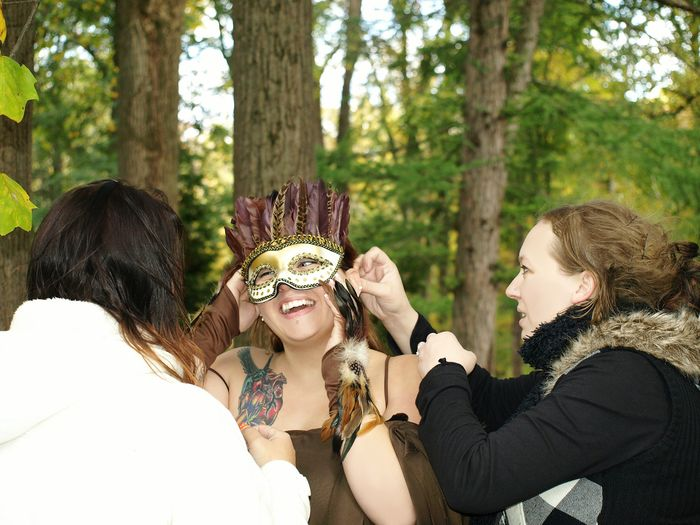 Female Friends Wearing Mask To Woman Against Trees In Forest