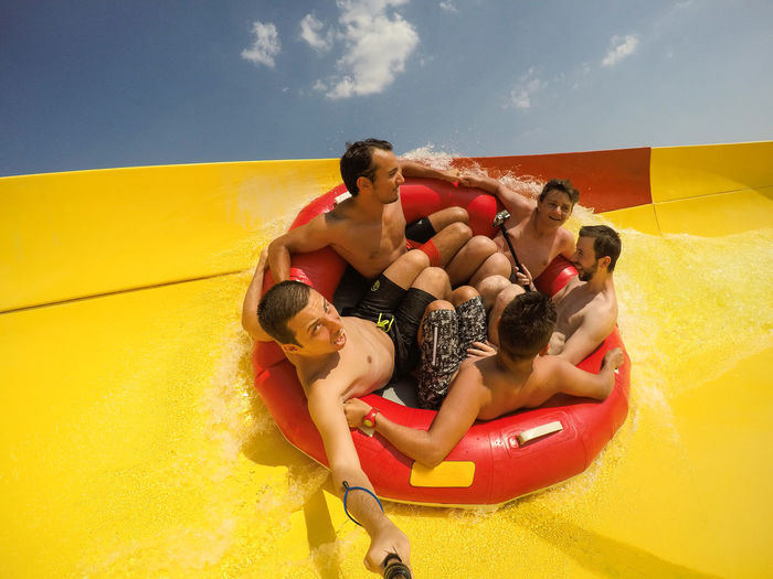 Friends sitting in inflatable ring on slide against sky