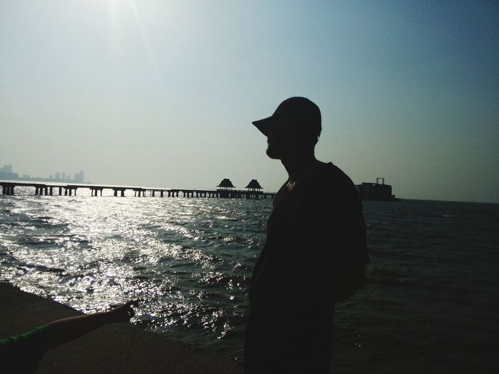 Silhouette of man at beach with pier in background