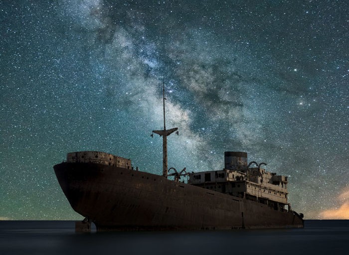 Scenic view of galaxy over old ship moored on sea at night