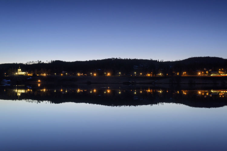 Reflection of illuminated trees in lake against clear blue sky