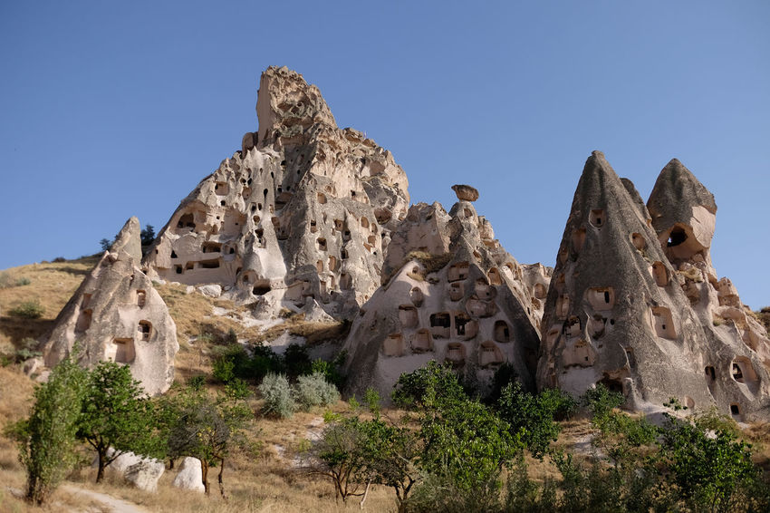 Homes mage out of rock in Uchisar, Cappadocia, Turkey Cappadocia Turkey Ancient Arid Climate Beauty In Nature Clear Sky Day Geology Low Angle View Nature No People Outdoors Physical Geography Rock - Object Rock Formation Scenics Tranquil Scene Tranquility Travel Destinations Uçhisar