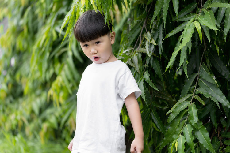 Cute boy standing against plants