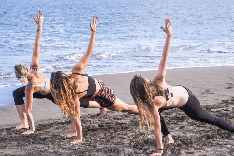Young friends doing yoga at sandy beach